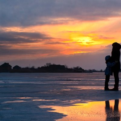 adult and child hugging on beach