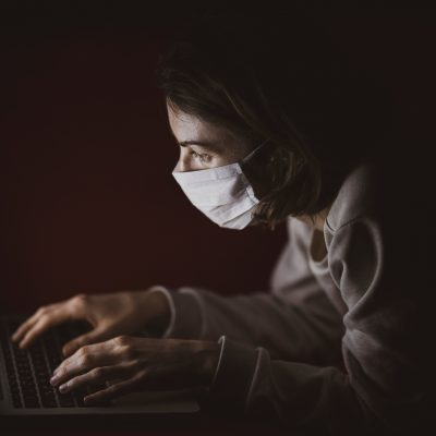 Person in dark on computer wearing mask